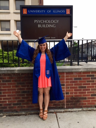 Emily Newton in a cap and gown in front of the Psychology Building.