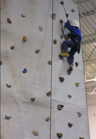 Someone climbing on a climbing wall in a gym