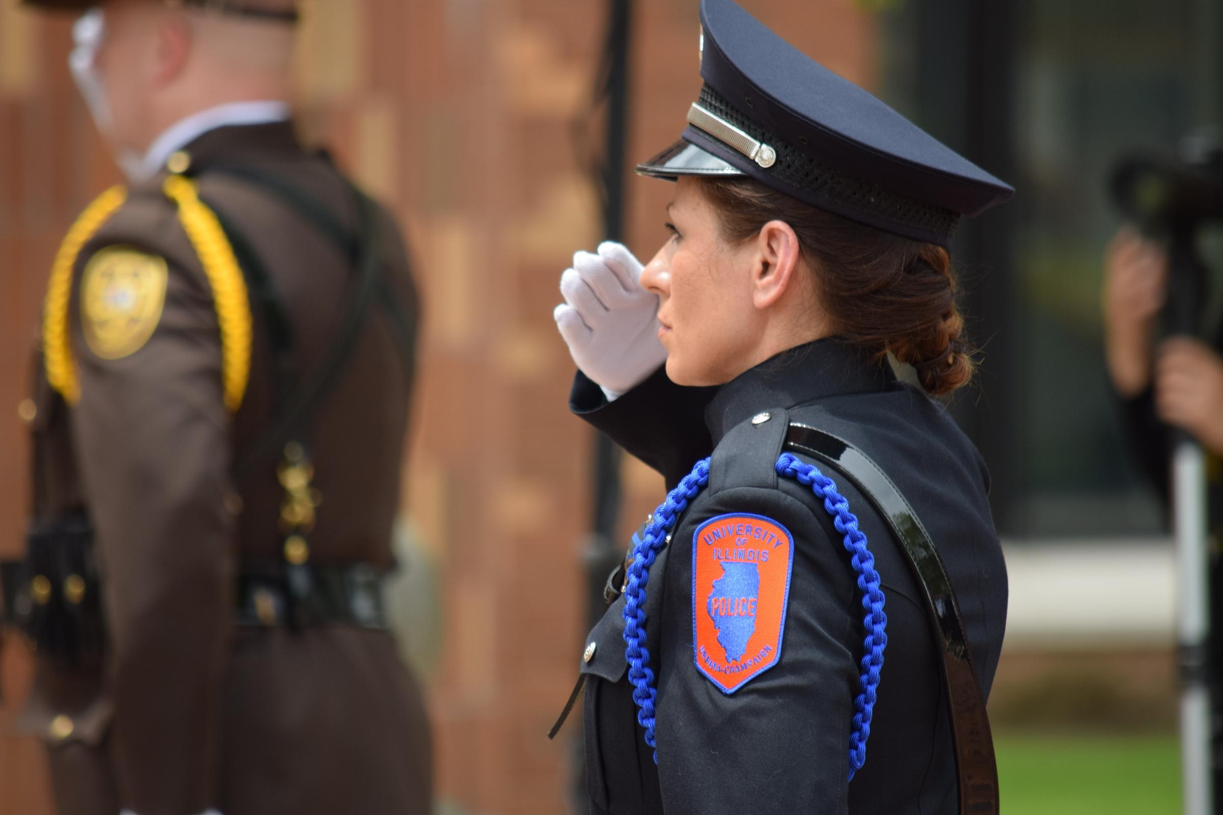 Female UIPD officer saluting.