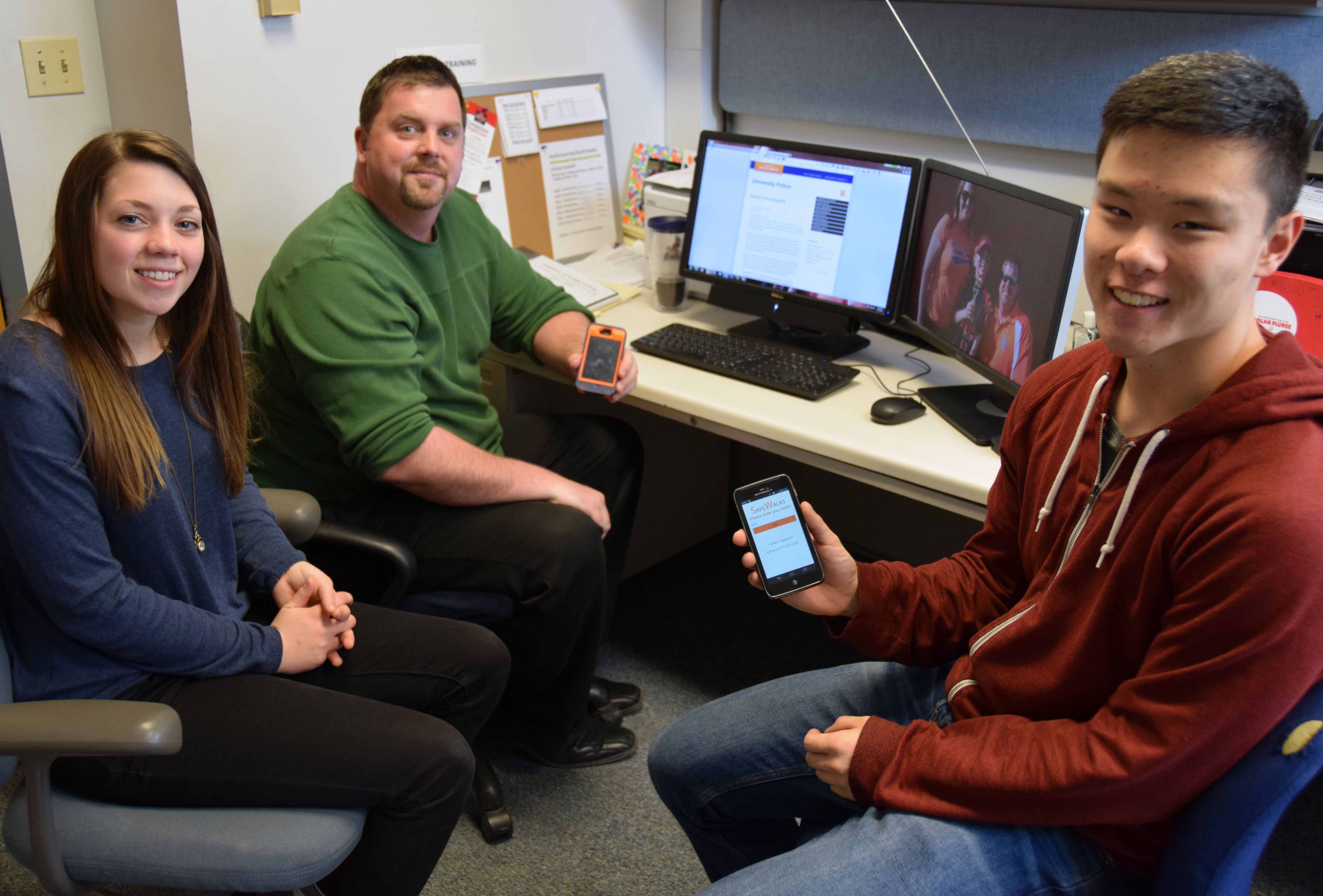 From left: U. of I. student patrol officer Taylor Franzen, Security Coordinator Ryan Johnson and U. of I. student patrol officer Michael Hao display the new SafeWalks app, which is to be released within the next few weeks.