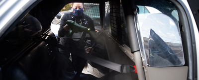 Officer Michelle Kaeding sprays vehicle with disinfectant.