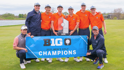 Coaches and team members hold a Big Ten Title banner