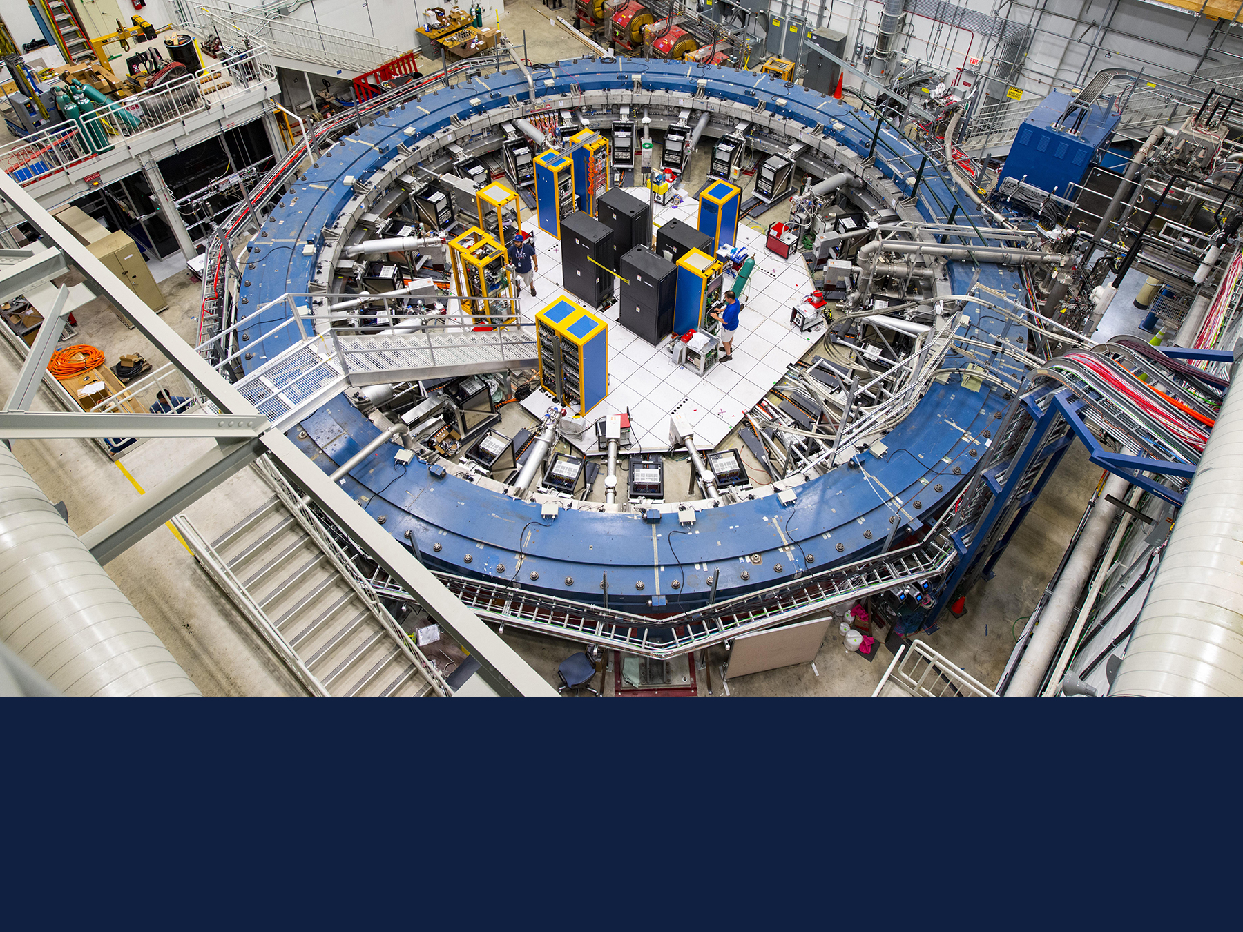 The Muon g-2 ring sits in its detector hall amidst electronics racks, the muon beamline, and other equipment. This impressive experiment operates at negative 450 degrees Fahrenheit and studies the precession (or wobble) of muons as they travel through the magnetic field. Photo by Reidar Hahn/Fermilab