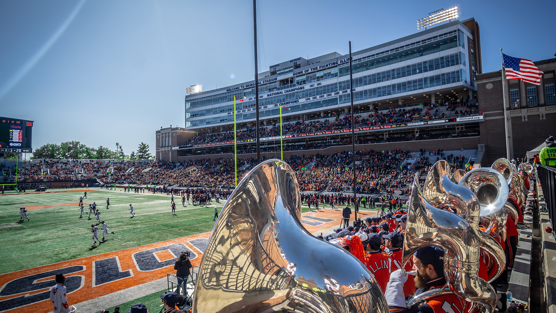 gameday scene at Memorial Stadium includes players on the field and Marching Illini Sousaphones in the stands
