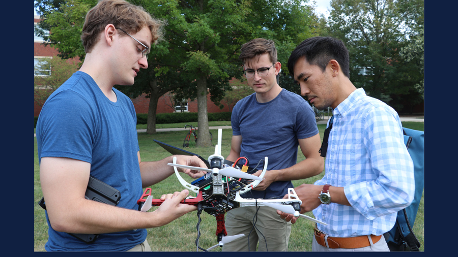 Neale Van Stralen, Ayberk Yaraneri, and Huy Tran test a drone on the U of I campus. (2019)
