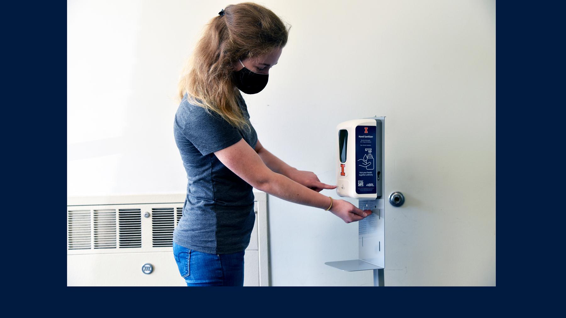 Illinois student uses hand sanitizer station labeled with U of I logo