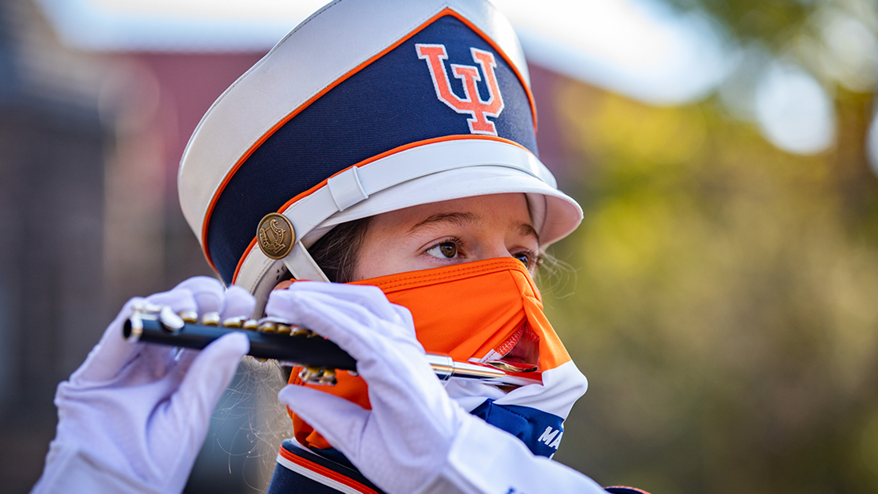 A piccolo player performs with the Marching Illini  wearing special masks designed with an opening that accommodates an instrument mouthpiece.