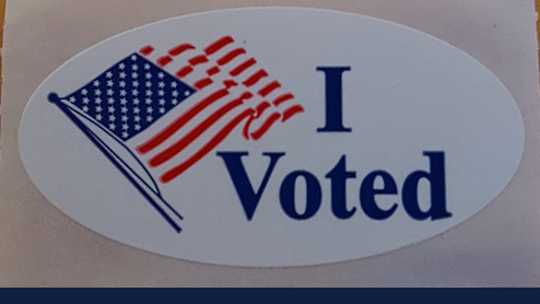 "sticker shows the American flag and the words, ""I voted"". Image via Wikimedia Commons"