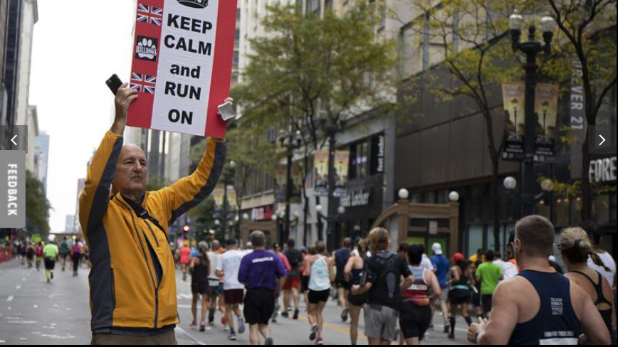 """man hold sign reading """"Keep Calm and Run On"""" as marathoners pass"""