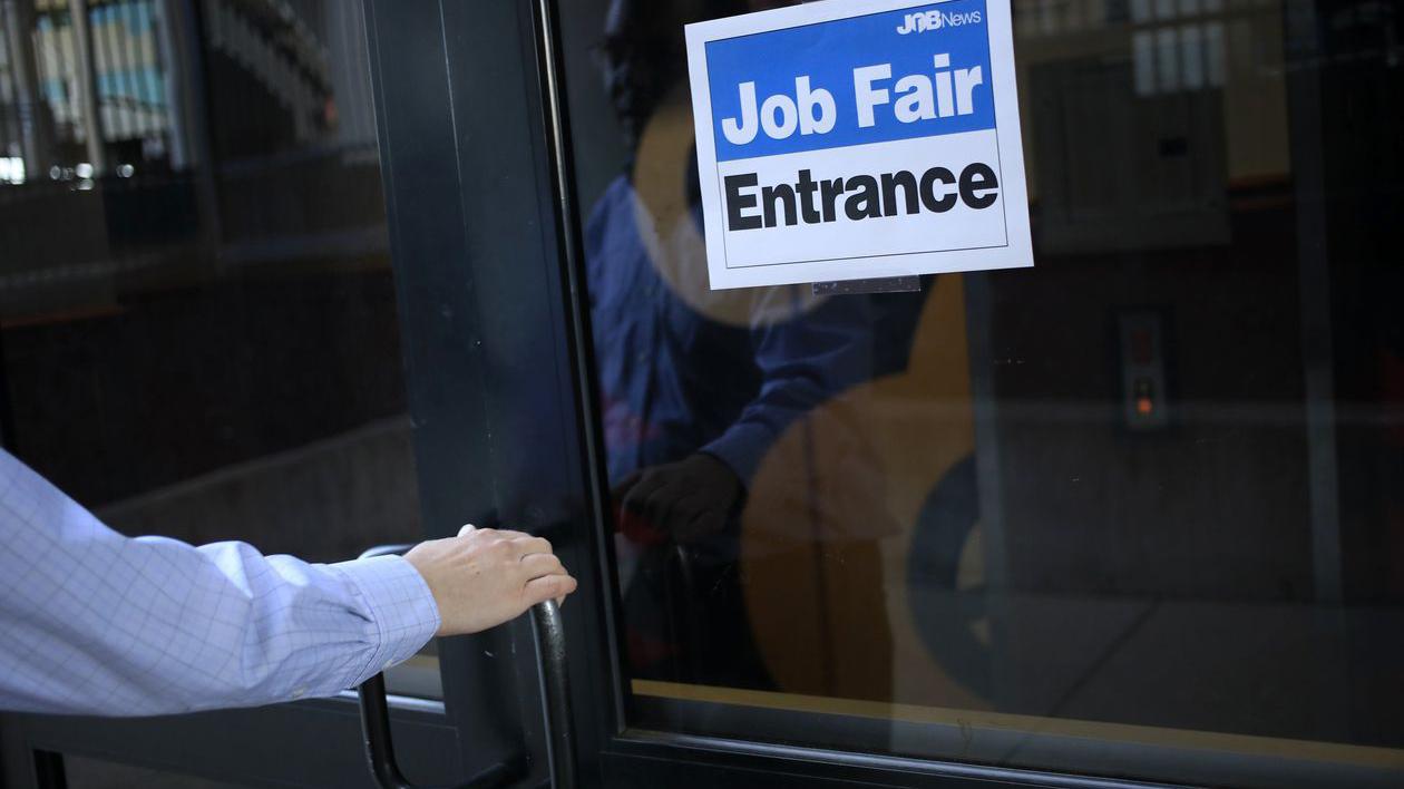 hand opens door to a job fair. Photo by Luke Sharrett for Bloomberg News