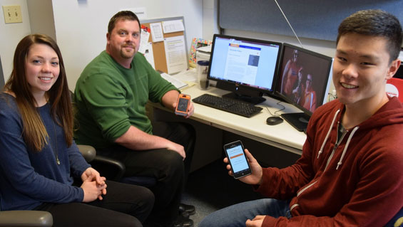 U. of I. student patrol officer Taylor Franzen, Security Coordinator Ryan Johnson and U. of I. student patrol officer Michael Hao display the new SafeWalks app, which is to be released within the next few weeks.