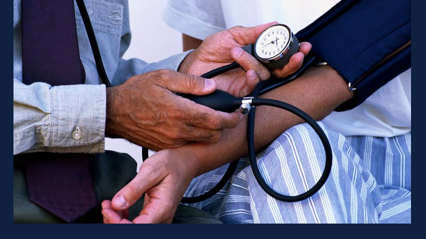 brown-skinned arm has blood pressure checked. Image via Wikimedia Commons