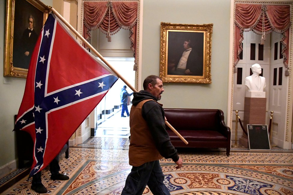 Man carries a Confederate battle flag inside the United States capitol. Photo by Mike Theiler / Reuters
