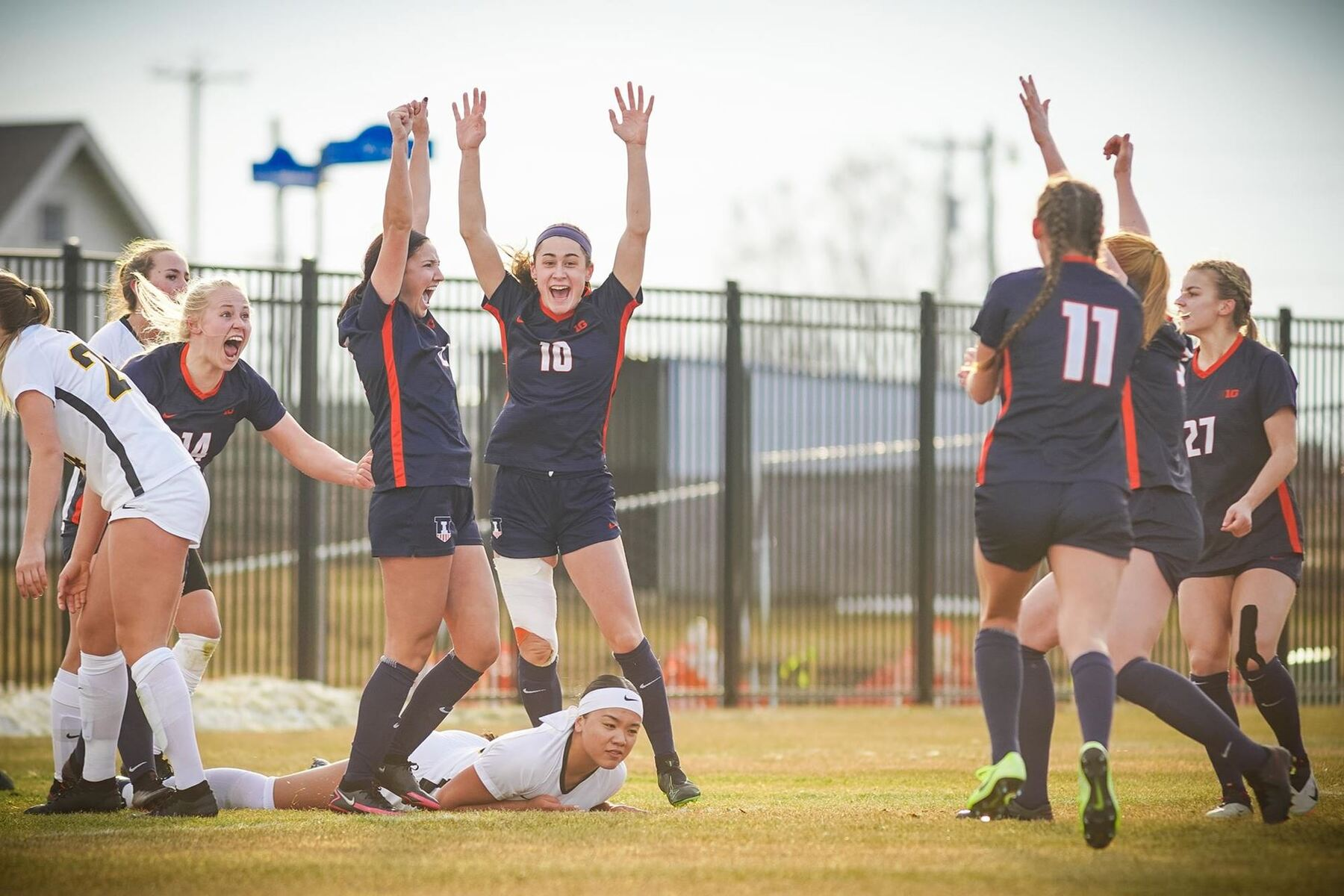ecstatic Illini Soccer players run towards each other in celebration of a goal