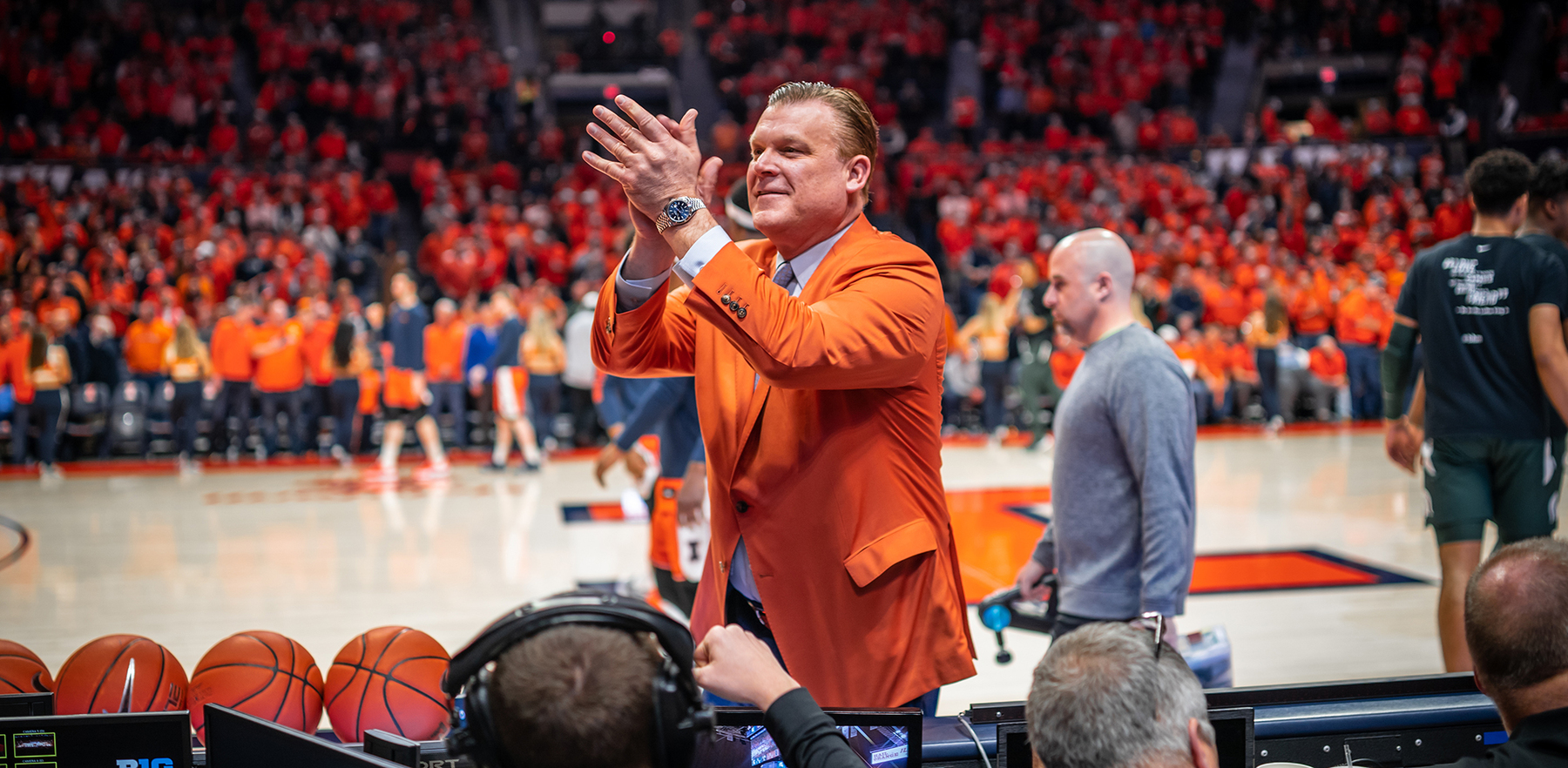 Illinois Coach Brad Underwood claps as he walks courtside in an orange blazer