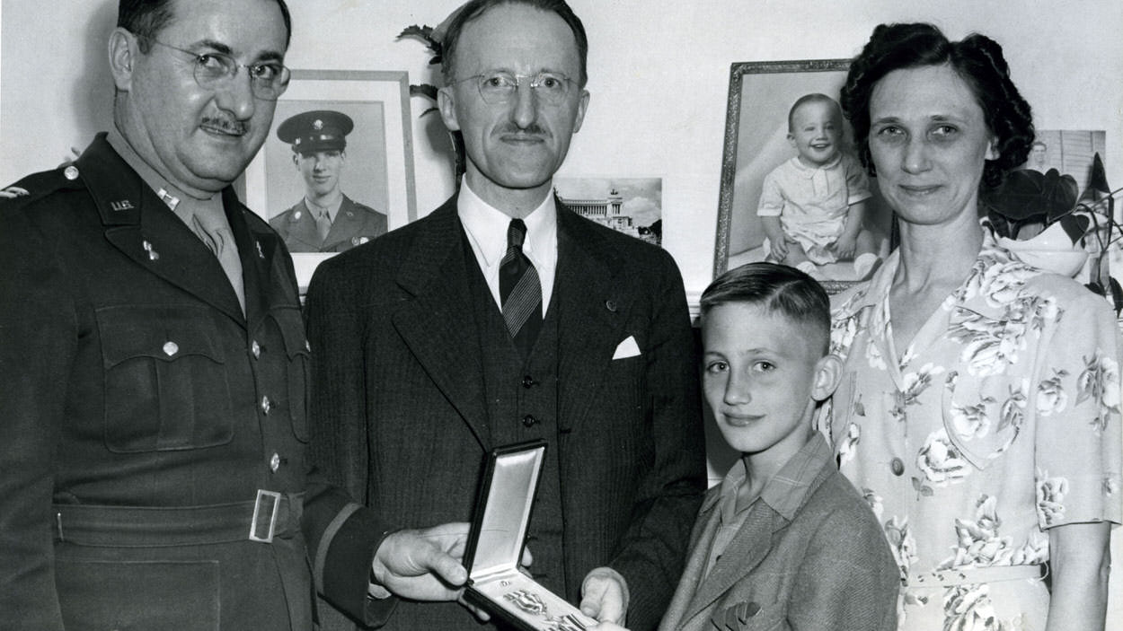 Pictured is the Snively family, posing with former Illinois student James Snivelys Silver Star award. From left to right: Captain Marietta, Jamess dad John R. Snively, his brother William H. Snively (Billy) and his mother Mabel Ruth Snively.