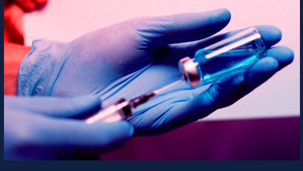 gloved hands fill a syringe