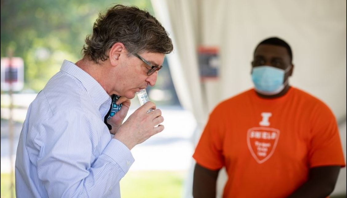 Illinois faculty member spits a saliva sample into a vial. Photo by Fred Zwicky