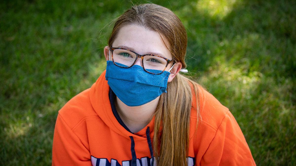 Ilinois student sitting outside wearing a mask.