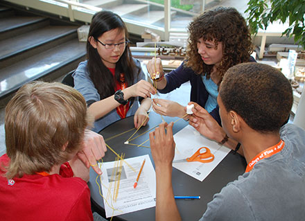 Margaret Hillengas, of Oak Park, and Laura Burns and Elijah King, both of Bloomington, work on building a structure from spaghetti, marshmallows, tape and string, during an activity in the 2014 Discover Architecture program.