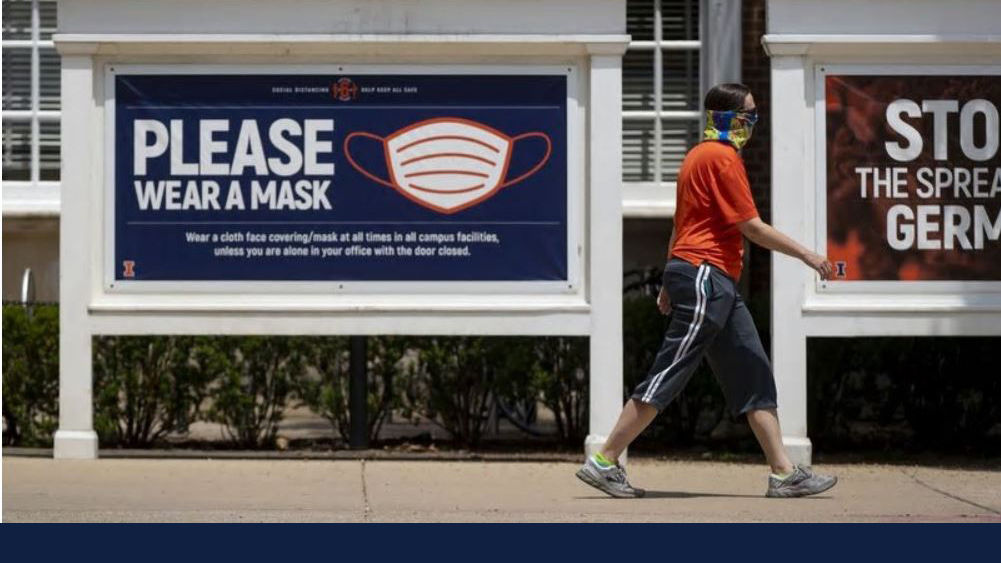 masked student walks by signage urging the use of masks. Photo by Brian Cassella / Chicago Tribune
