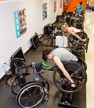 Image of athletes using roller machines fitted with Kickr bicycle trainers to add resistance.