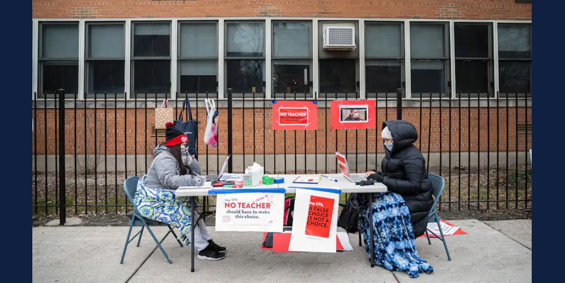 Teachers Adrienne Thomas and Irene Barrera set up outside Suder Montessori Magnet Elementary School in Chicago on Jan. 11 in solidarity with pre-K educators who had to return to work in the building. (Anthony Vazquez/Chicago Sun-Times/AP)