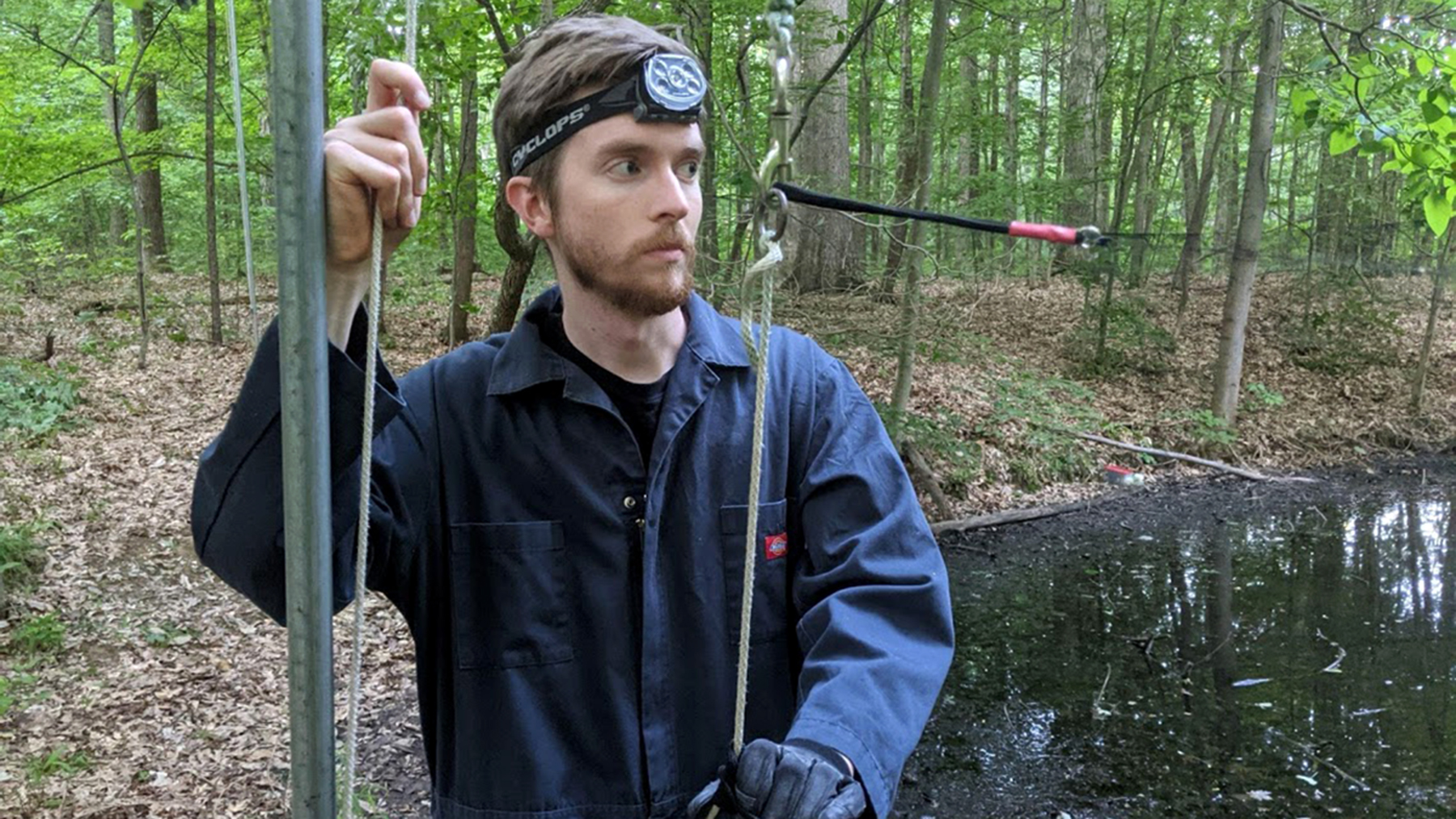 The author helps his colleagues install mist nets around a pond. ALT TEXT: Photo of the author standing near a vertical pole used to secure the nets. He grasps a cord used to tighten the nets in place.  Photo by Elizabeth Beilke