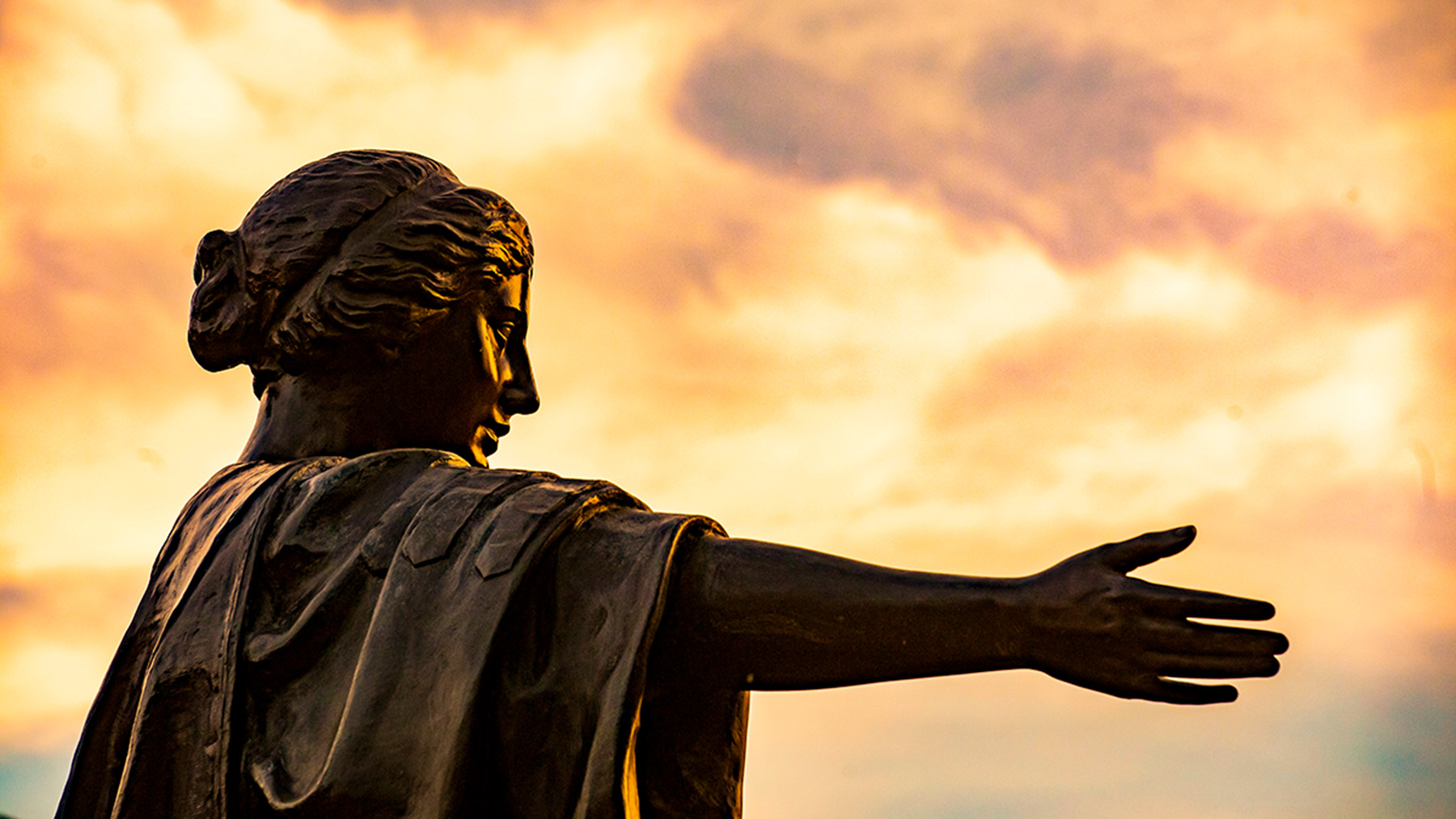 Alma Mater Statue in light of a cloudy orange sunset. Photo by Fred Zwicky