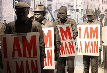 image of sculptures of men, each carrying 'i am a man' sign
