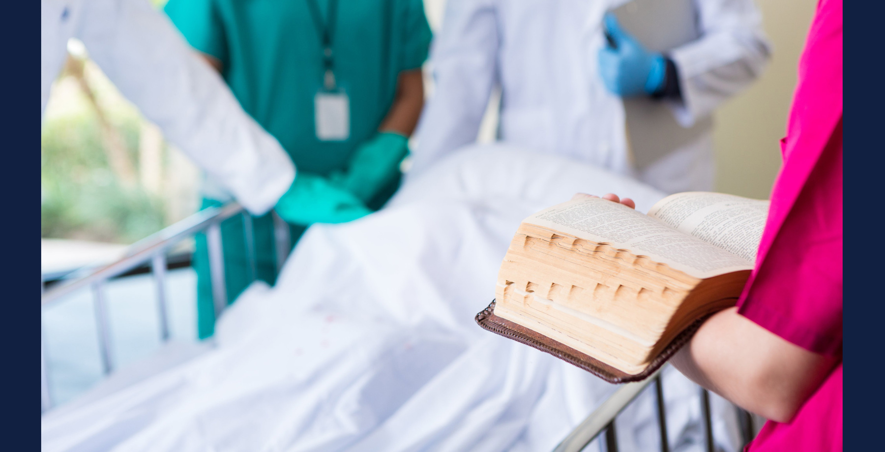stock image of chaplain and hospital staff attending to a patient