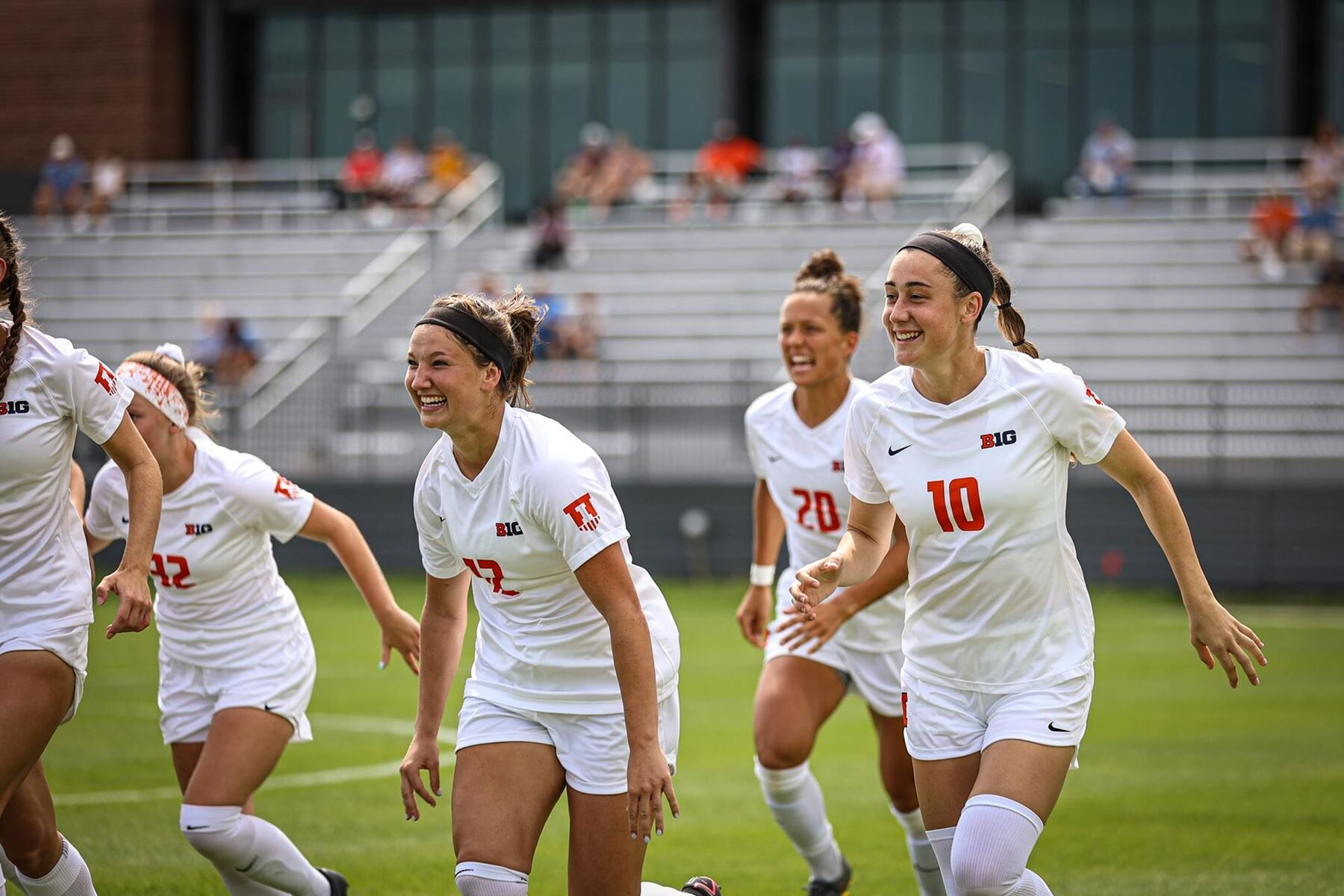 Smiling Illini Soccer players run off the field