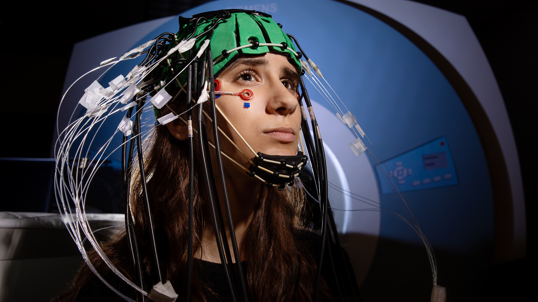 A young woman inside an MRI suite wears an imaging cap with many sensors attached.
