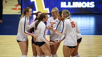 illini volleyball players huddle to celebrate a point in a previous game