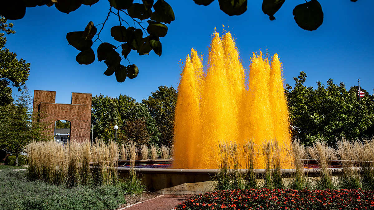 Fountain, died orange, with Hallene Gateway in the background