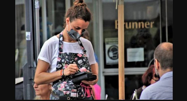 waitress wearing a face covering serving a customer outside. Image via Pixabay