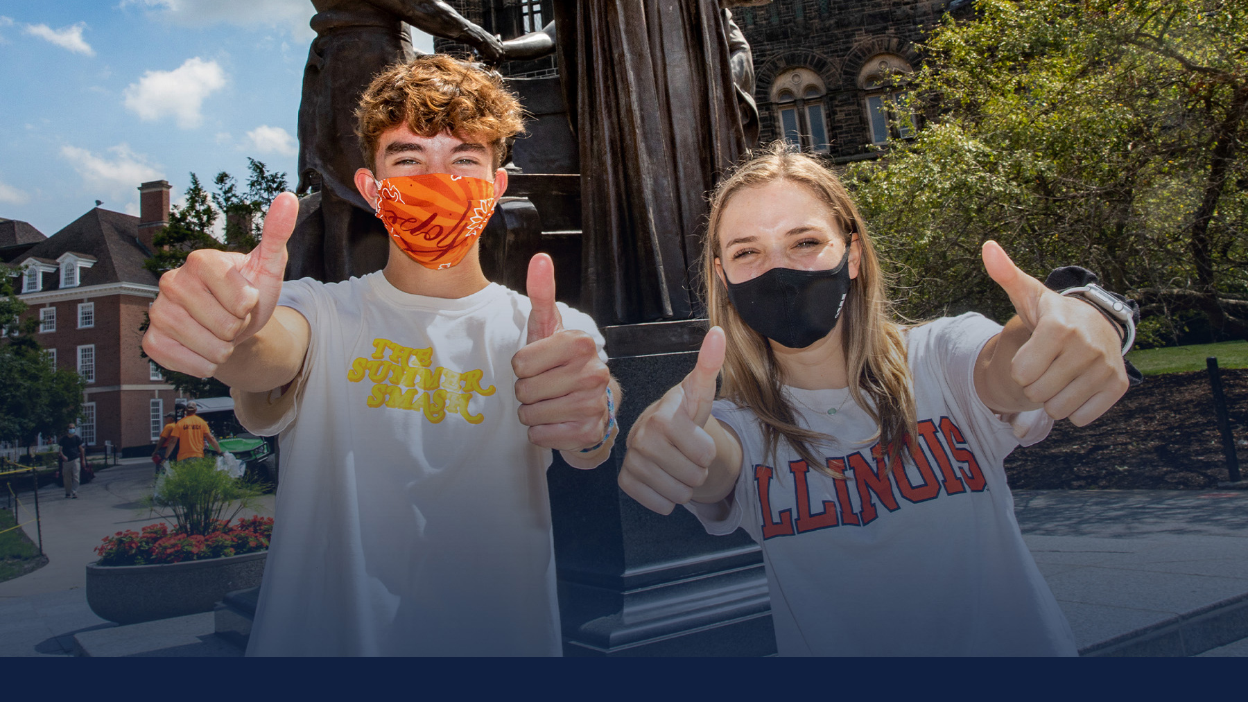 students wearing masks stand in front of the Alma Mater statue