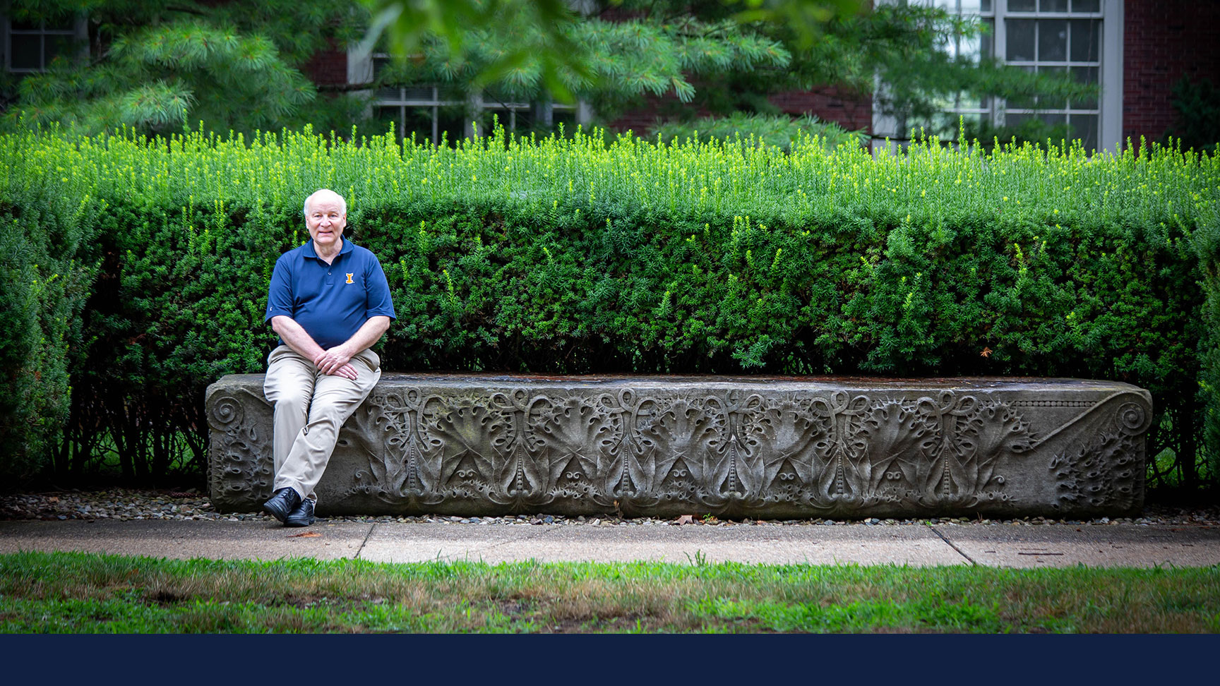 Dennis Craig sits at the ornately carved granite bench north of the Architecture Building.