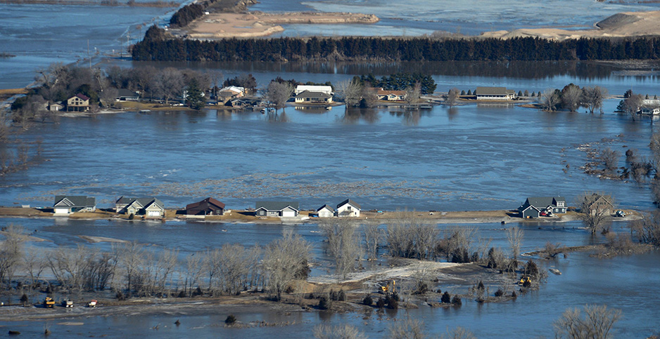 Homes in Nebraska are surrounded by floodwater last year. The Trump administration is delaying work on the National Climate Assessment. SrA Jamie Titus/UPI/Newscom