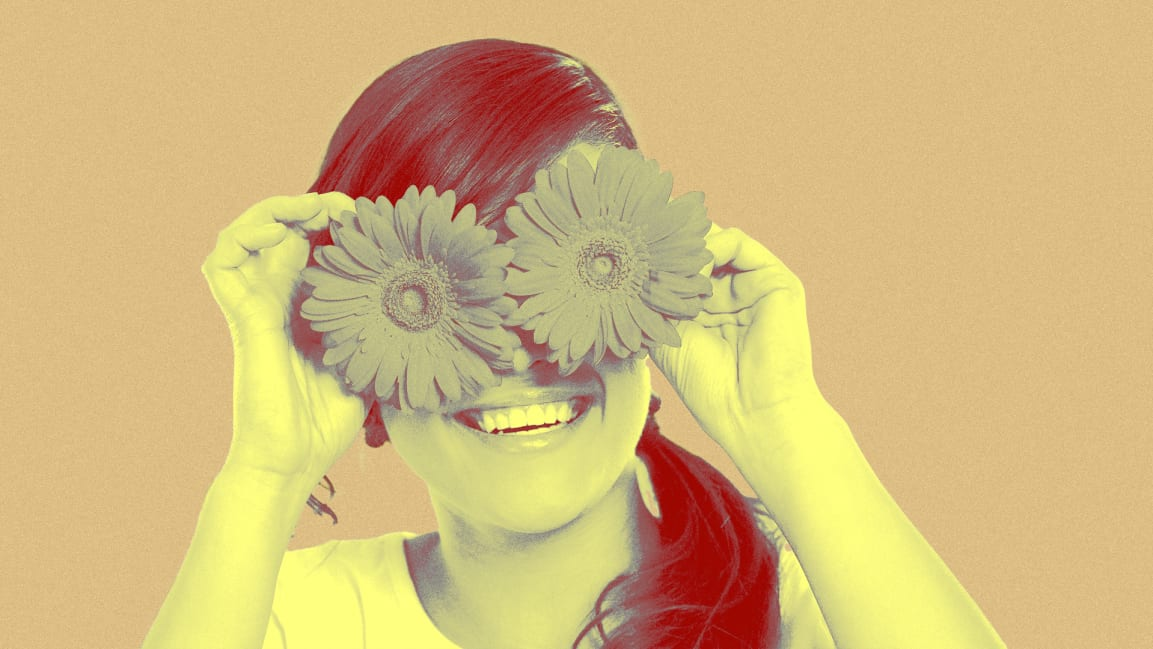woman  holding flowers up where her eyeballs ought to be. Image from gpointstudio/iStock