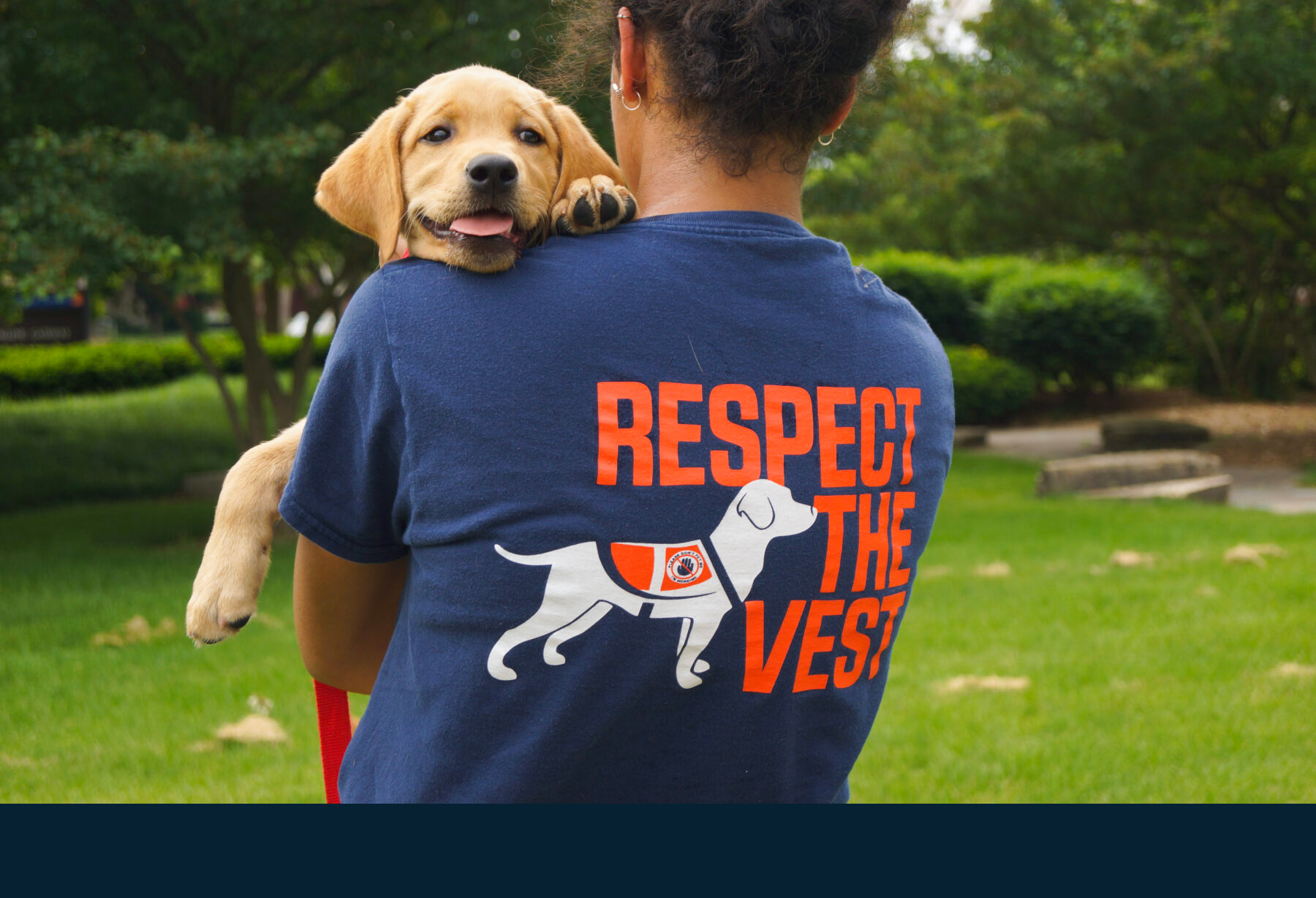 "Illini Service Dogs volunteer wearing ""respect the vest"" t-shirt carries a puppy"