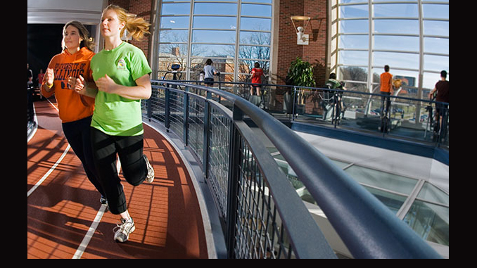 two women run on indoor track. Photo by Brian Stauffer