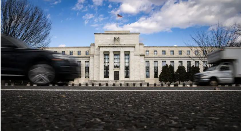 Vehicles pass in front of the Marriner S. Eccles Federal Reserve Board Building in Washington on Jan. 22. (Al Drago/Bloomberg)