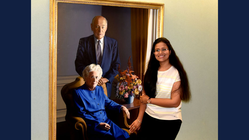 Mittal poses beside a portrait of Arnold and Mabel Beckman, two of the many mentors who provided inspiration throughout her Ph.D. program.