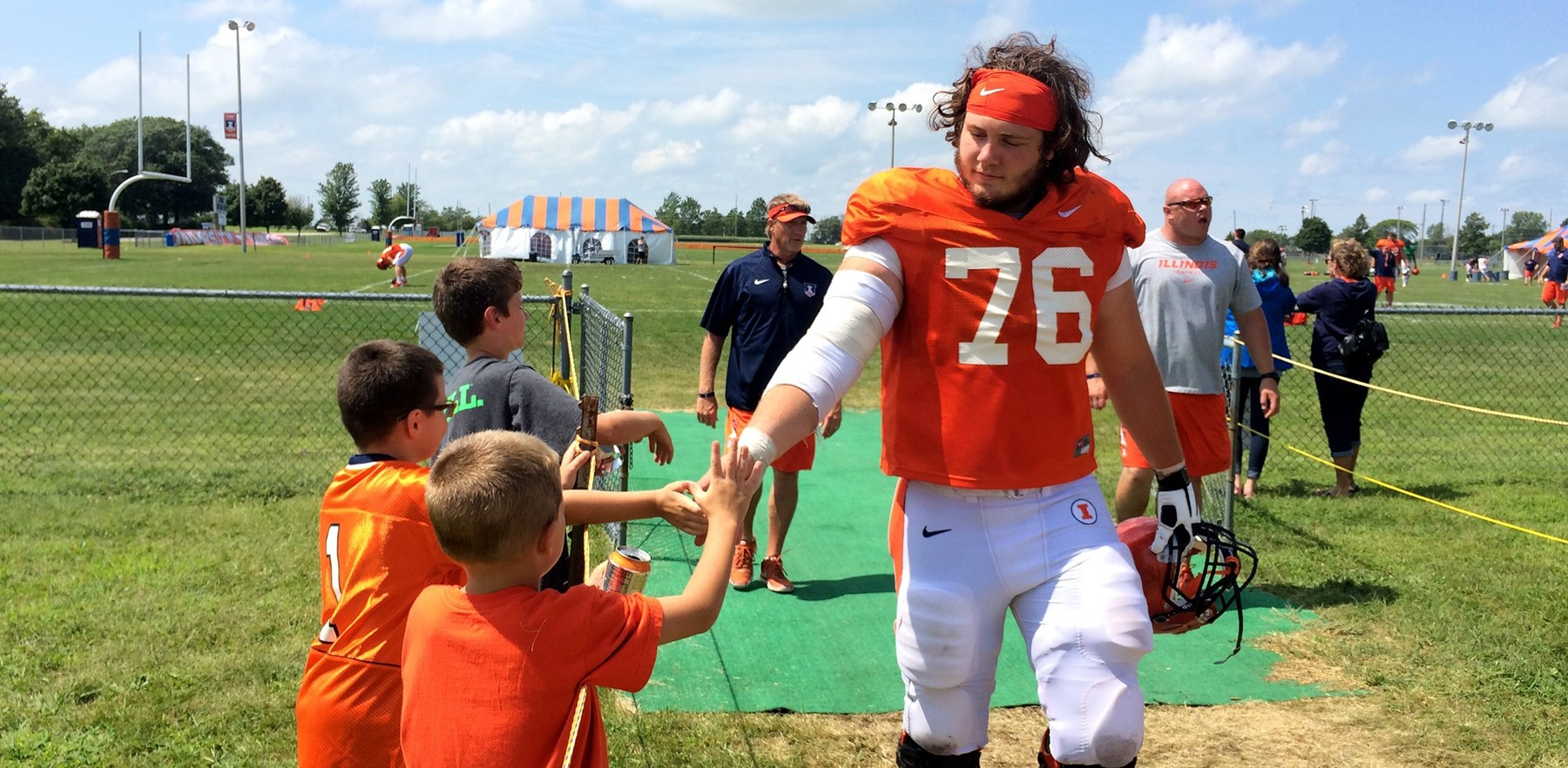 image of Illinois offensive linebacker zeke martin high-fiving young fans
