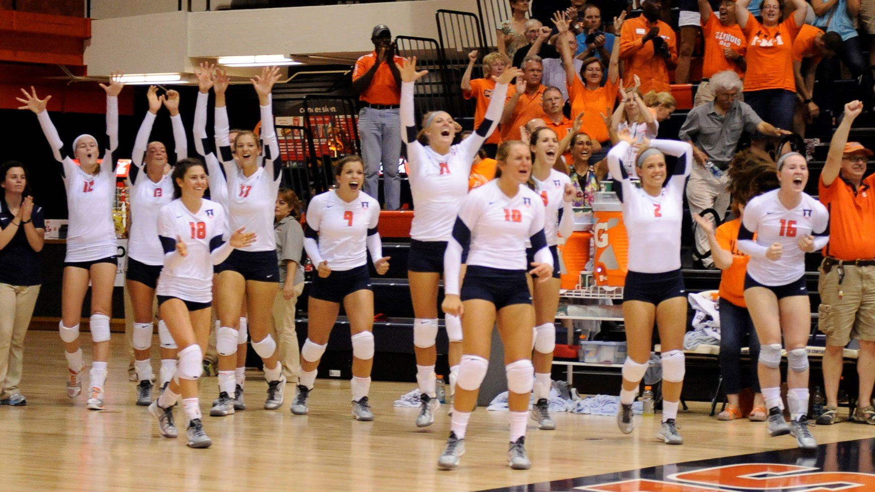 image of illini volleyball team celebrating a win