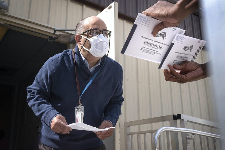 Election workers in Pennsylvania, like the one seen here, couldn't begin verifying mail-in ballots until Election Day, meaning there may be significant delays before full results are available. AP Photo/Laurence Kesterson