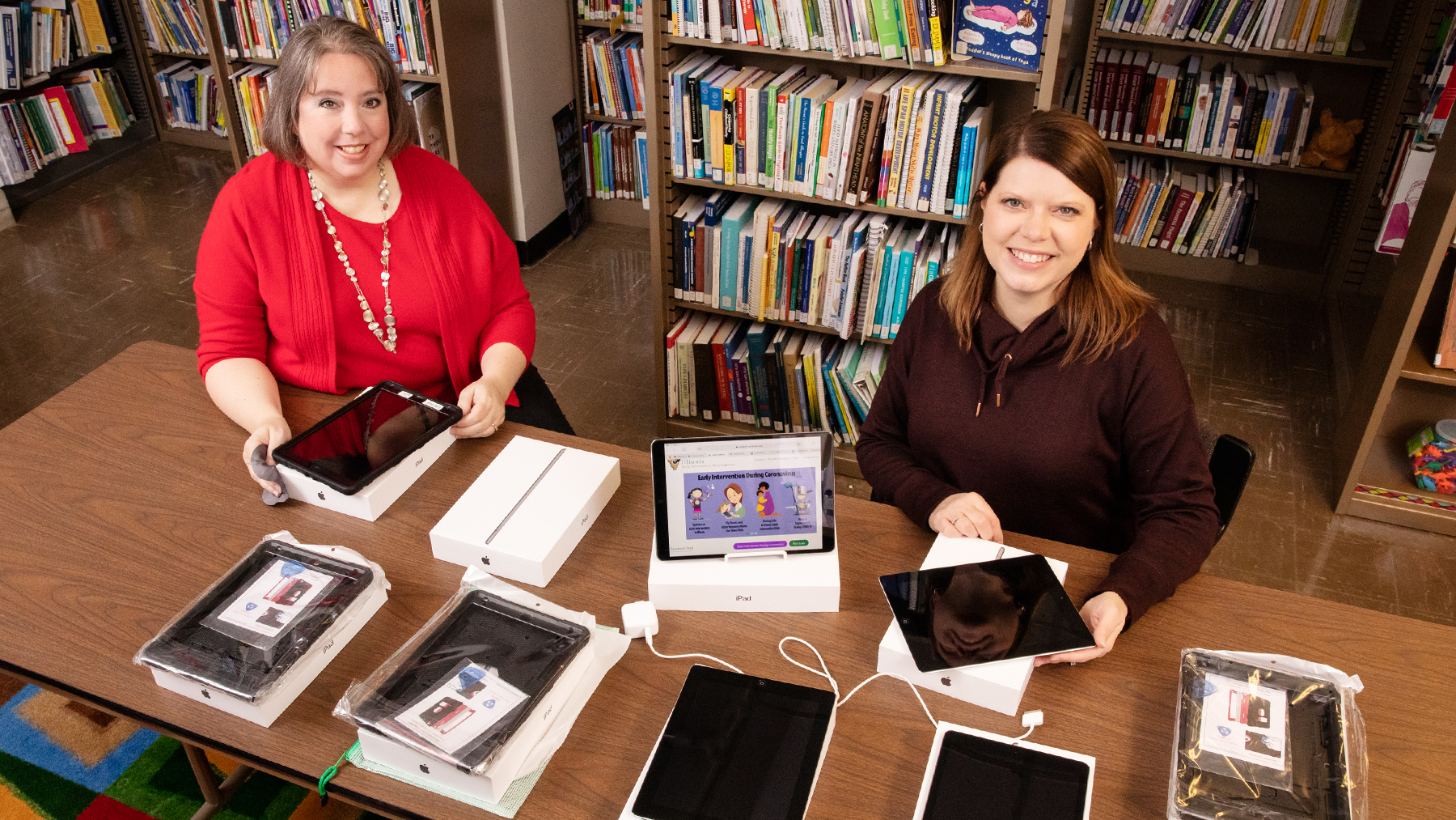 Sarah Isaacs, the librarian of the Early Intervention Clearinghouse, and research information specialist Jill Tompkins show some of the tablet computers and Wi-Fi hotspots that families of infants and children with disabilities or delays can borrow for telehealth visits with providers of early intervention services.