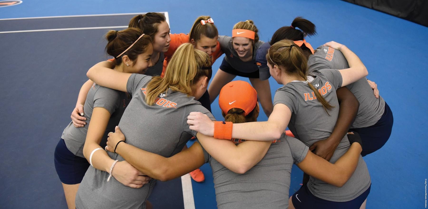 image of Illini tennis players huddling and smiling