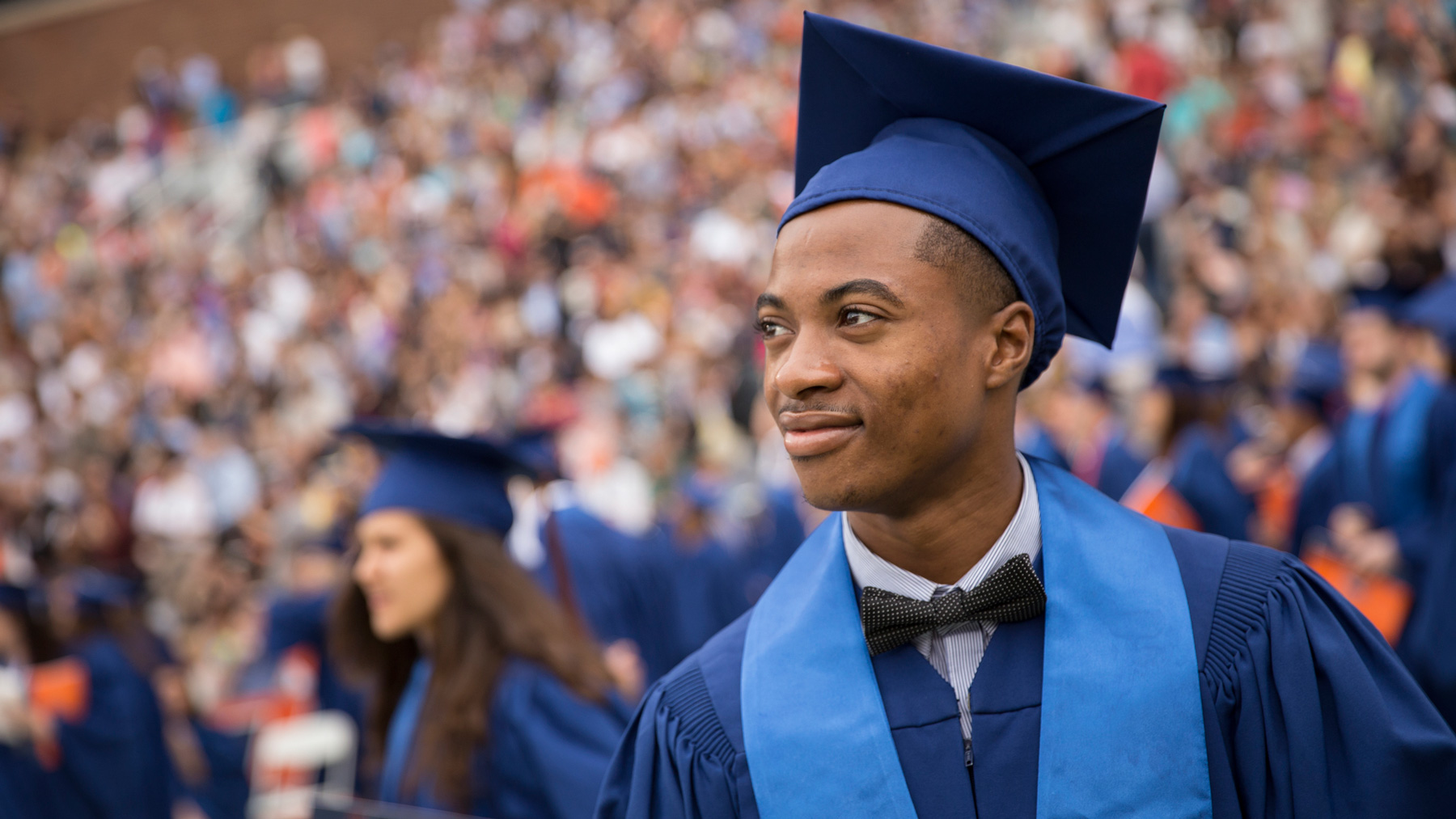 smiling, bow-tied graduate at commencement